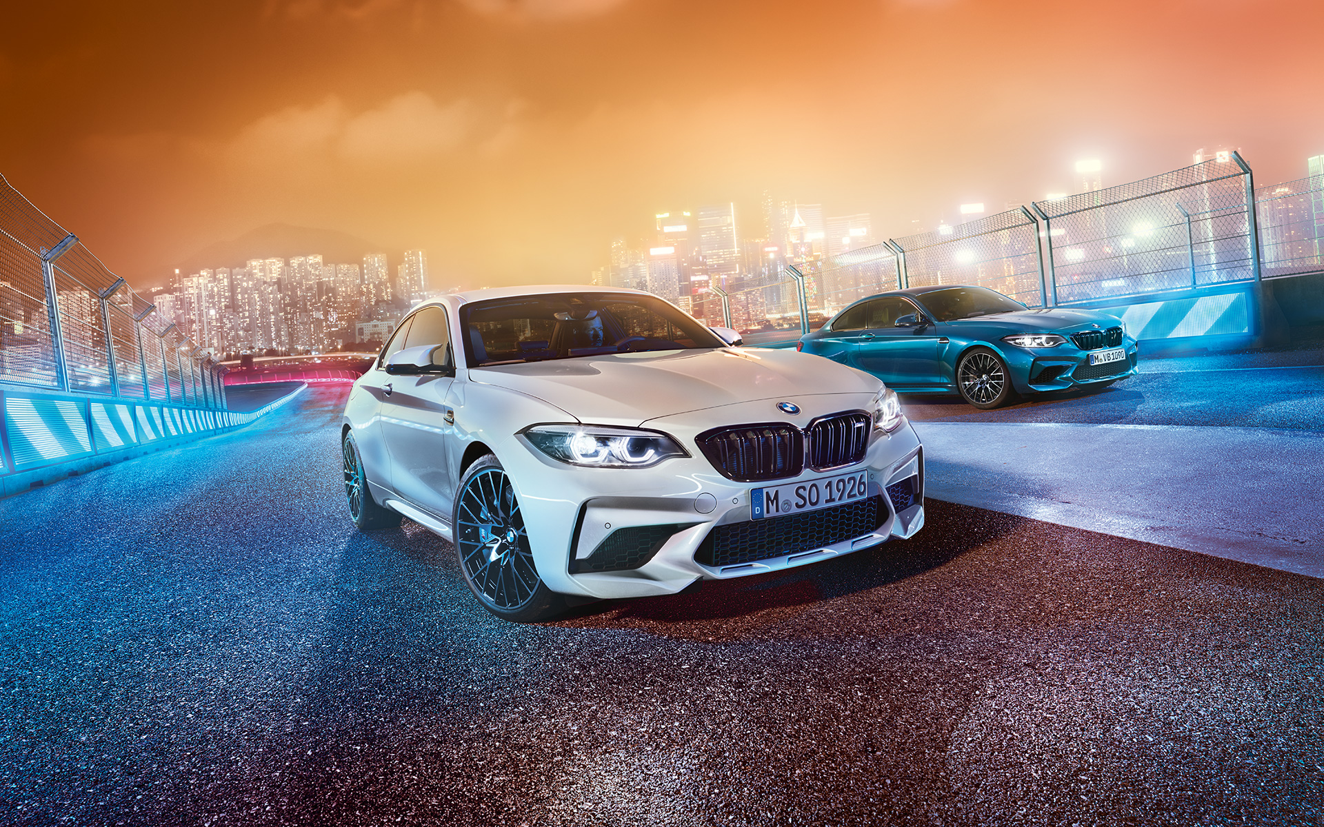 White and blue BMW M2 Competition standing on race track in front of nocturnal cityscape.