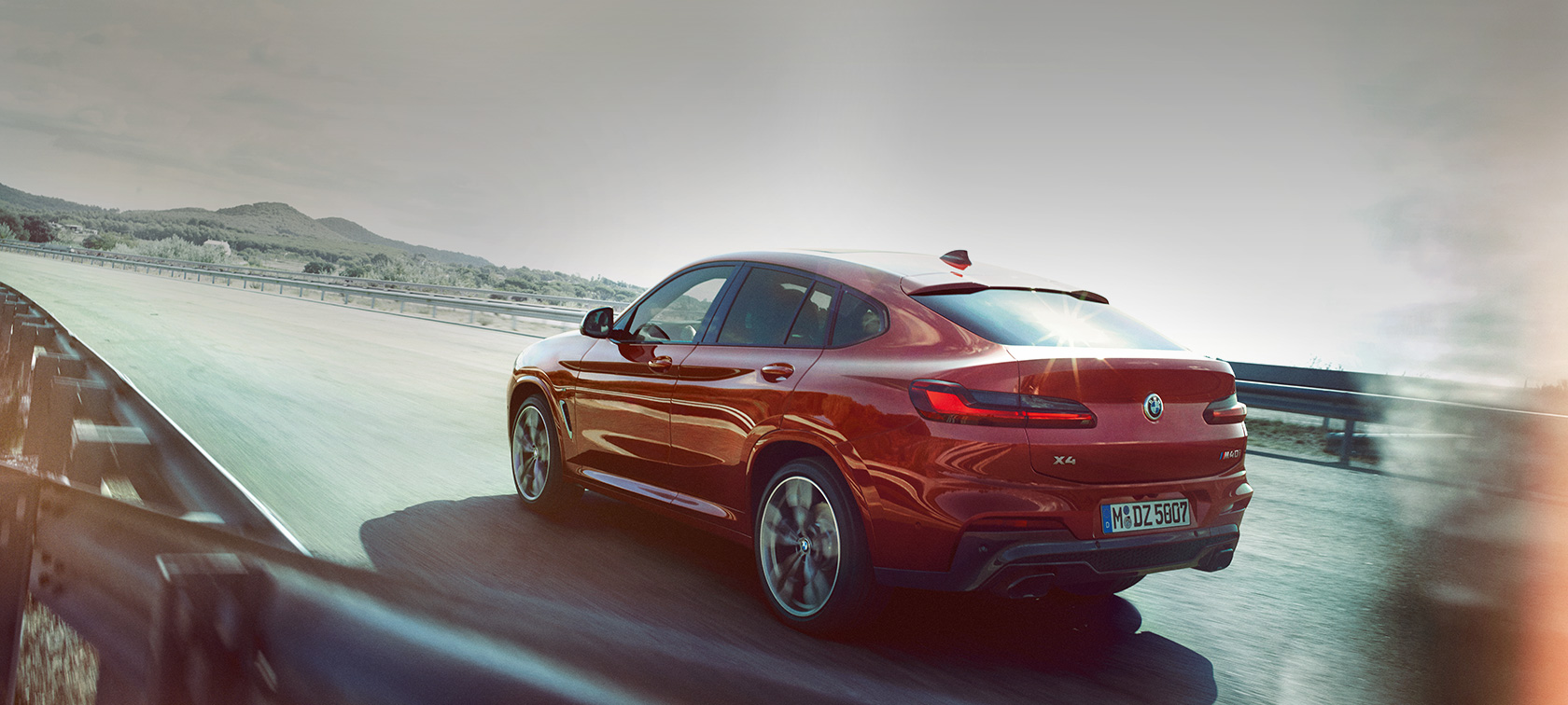 BMW X4 M40i G02 2018 toonis Flamenco Red Brilliant Effect, 3/4 tagantvaade, teel sõitmas